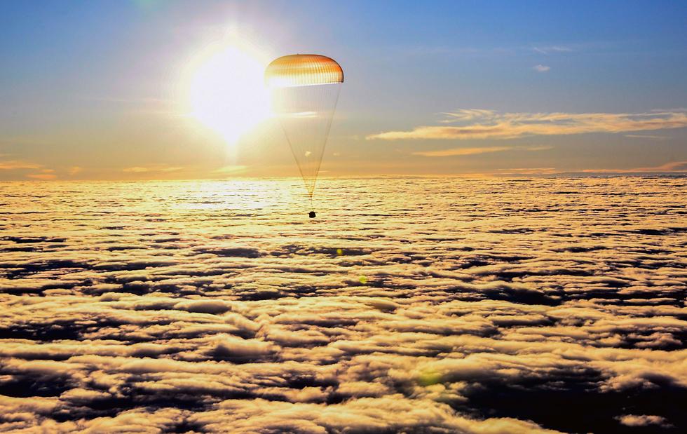 אנשי צוות תחנת החלל הבינלאומית חוזרים לכדור הארץ עם קפסולה שנשאה אותם ונוחתים בקזחסטן (צילום: AFP) (צילום: AFP)