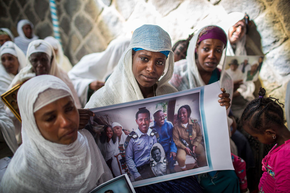 חברי הקהילה היהודית באדיס אבבה, אתיופיה, מחזיקים בתמונות בני משפחה שחיים בישראל. סוכנות הידיעות AP דיווחה שאלפי בני הפלשמורה שנותרו באתיופיה מאיימים בשביתת רעב המונית אם ייפגע התקציב המיועד להבאתם ארצה (צילום: AP) (צילום: AP)