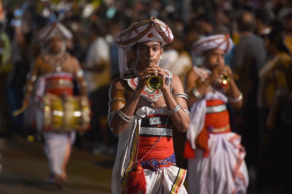 רקדנים בלבוש מסורתי משתתפים בטקס דתי במקדש גנגראמה שבקולומבו, סרי לנקה (צילום: AFP) (צילום: AFP)