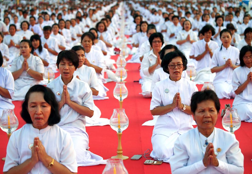 """מאמינים בודהיסטים בתפילה המונית בפאתי בנגקוק לרגל ה""""מאקה בוצ'ה"""" - יום הירח המלא שבמהלכו עורכים תפילות במקדשים, בהן תפילת הודיה לאל בודהה  (צילום: EPA) (צילום: EPA)"""