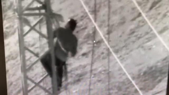 A Hamas operative climbing a high voltage line