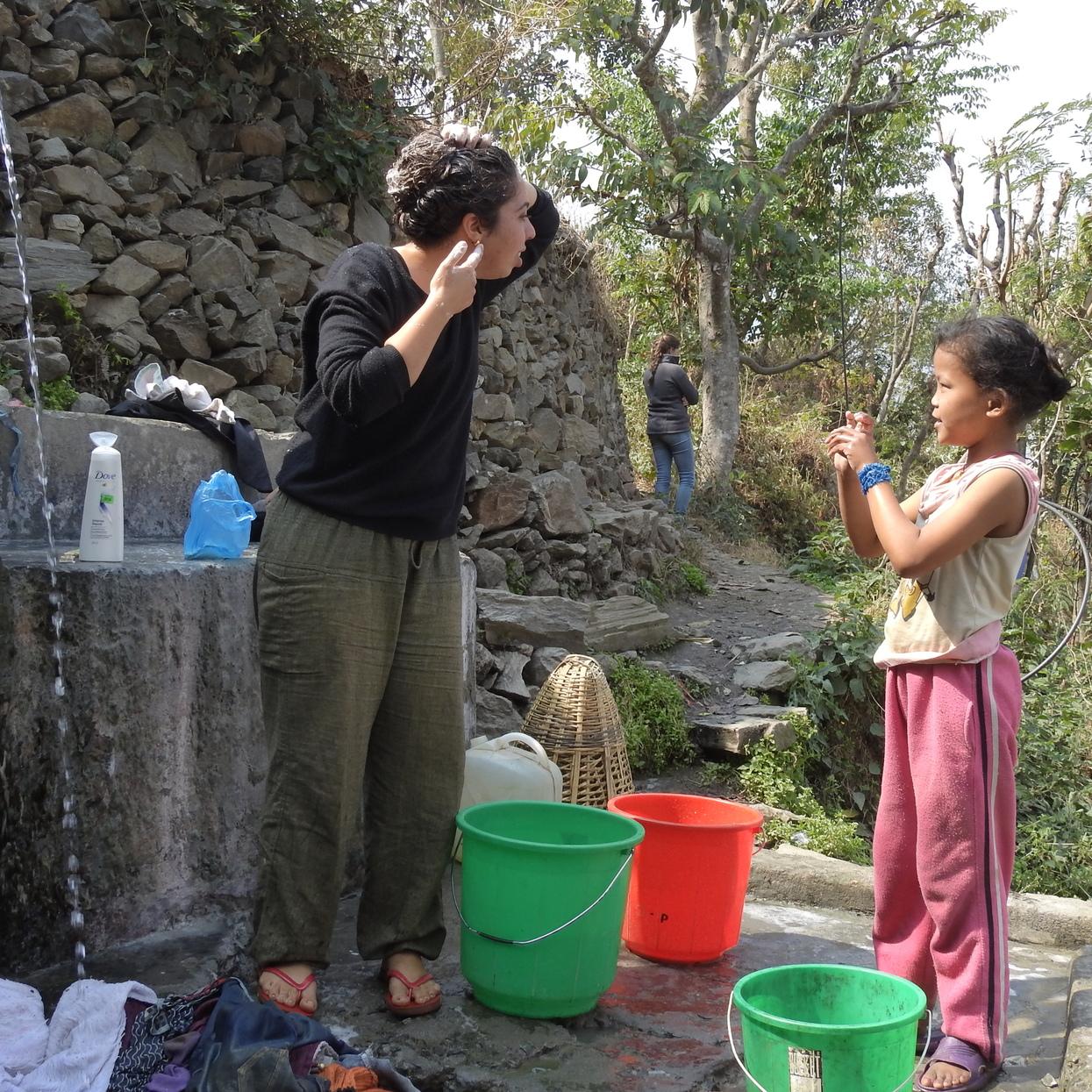 חופפות וכובסות. שני מנצלת את זמן הכביסה כדי לחפוף את הראש במעיין המים בכפר דהאו. צילום: עמיר בן-דוד