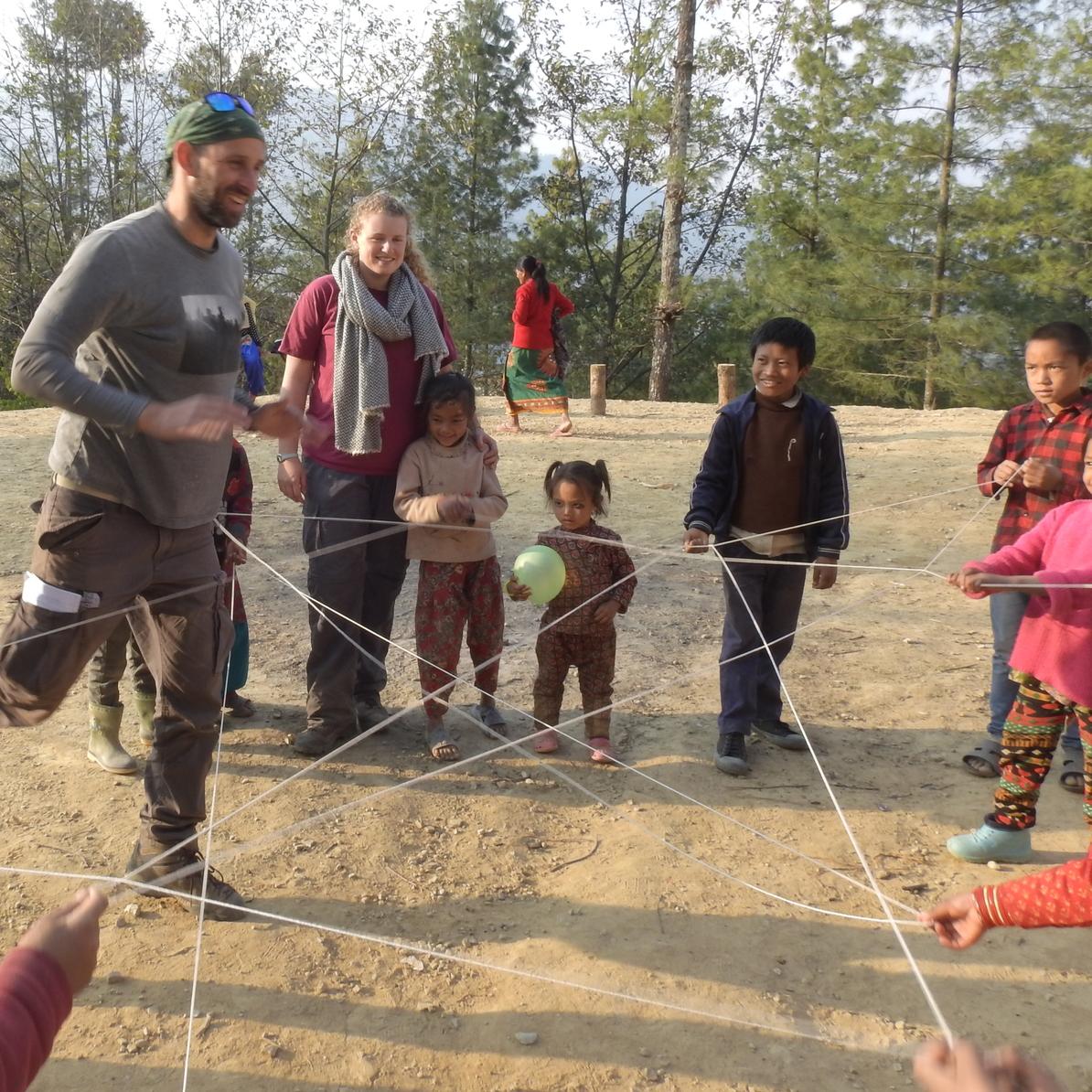 """רוני וג'וש, שניים ממתנדבי """"תבל"""", משחקים עם ילדים נפאליים בכפר דונקנרה. צילום: עמיר בן-דוד ()"""