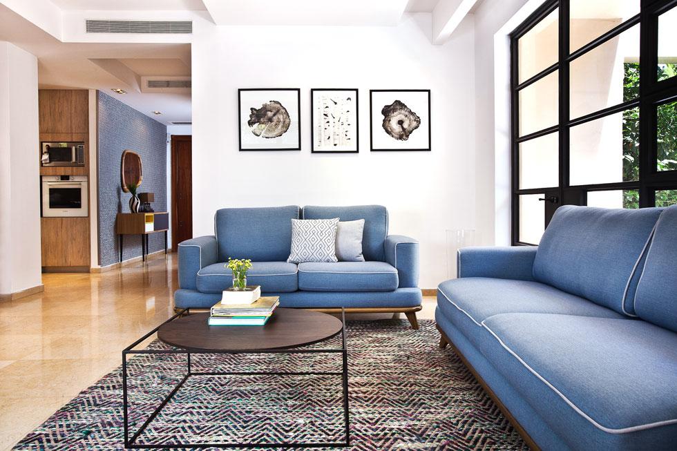 לסלון נרכשו שתי ספות ושטיח. שולחן הקפה יוצר בהזמנה. חלק מהתמונות על הקירות נבחרו מאוספים משפחתיים   (צילום: יונתן תמיר)