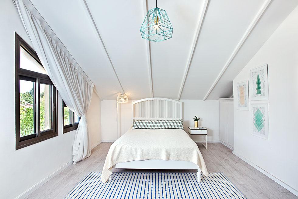 חדרה הבהיר של הבת הבכורה בעליית הגג. את נגיעות הצבע מספקים השטיח, המנורה התלויה והתמונות על הקיר  (צילום: יונתן תמיר)
