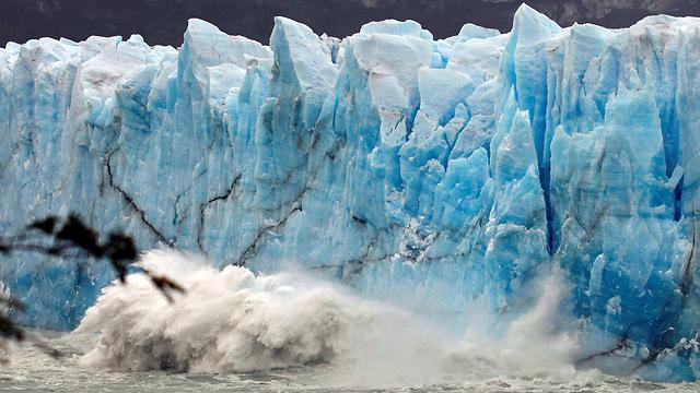"""גוש קרח צולל אל המים ב""""קרחון המתנפץ"""" (צילום: רויטרס) (צילום: רויטרס)"""