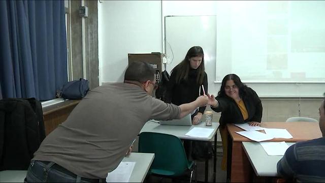 כיתה, תלמידים יושבים ומישהי עומדת ליד אחד מהם ומראה לו משהו על הלוח ()