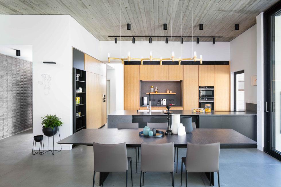 """המטבח בנוי בחלקו הסגור יותר של המרחב הציבורי, ובמרכזו אי גדול במיוחד. """"ביקשנו מהאדריכלים משטח שיש גדול"""", מספרים בני הזוג, """"כדי ששלושה אנשים יוכלו לעבוד עליו ביחד"""". למשל, שלושת הבנים, שמכינים לעצמם את הכריכים בכל בוקר  (צילום: עוזי פורת)"""