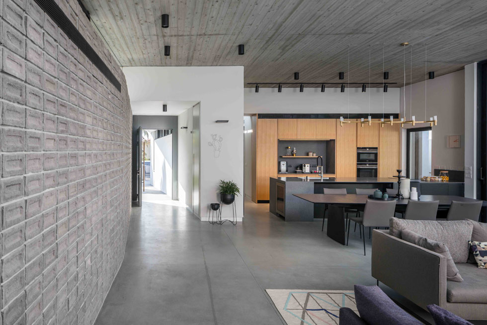 """בתוך הבית, הקיר בנוי מלבנים חצויות, ומלווה את כל החלק הציבורי. """"הלקוחות"""", מספרת האדריכלית ליחן אמיצי, """"רצו אלמנט ייחודי שאינו נגרות""""  (צילום: עוזי פורת)"""