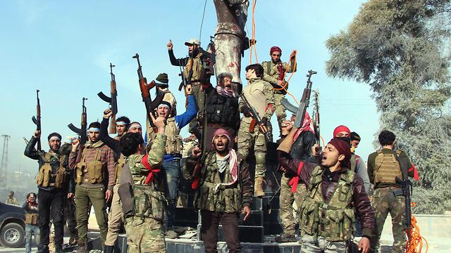 מורדים מצבא סוריה הפילו פסל כורדי ומניפים את דגלם (צילום: AP)