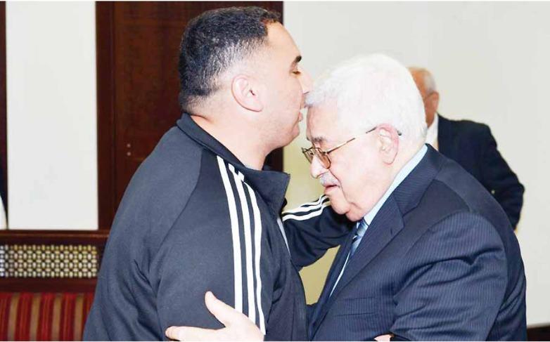 Raja Haddad (L) embraced by PA President Mahmoud Abbas (Photo: Al-Hayat al-Jadida)