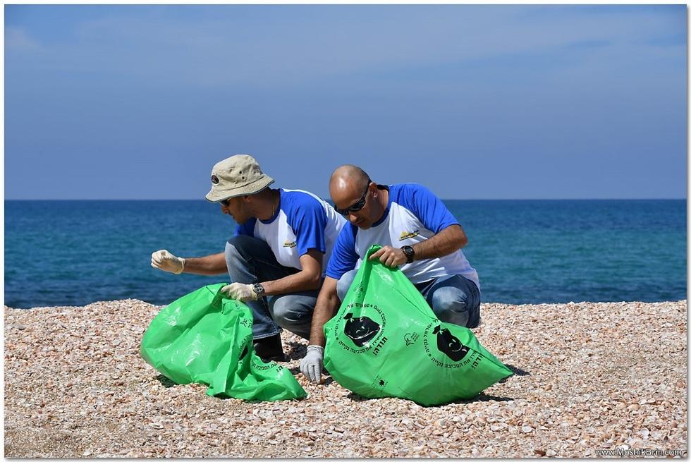 שני גברים אוספים זבל מהחוף שקיות ניילון גדולות  ()