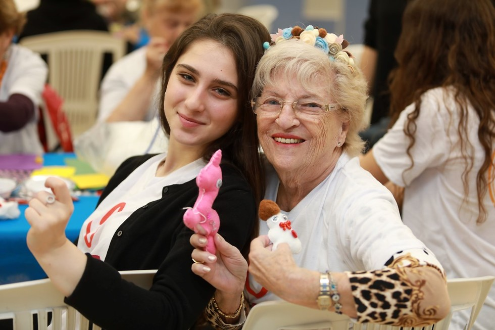 אישה מבוגרת וצעירה מציגות מלאכת יד משותפת , מחייכות ()