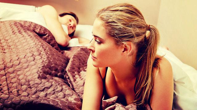 אישה שוכבת לצד בן זוגה ותוהה אם לבגוד בו (צילום: Shutterstock)