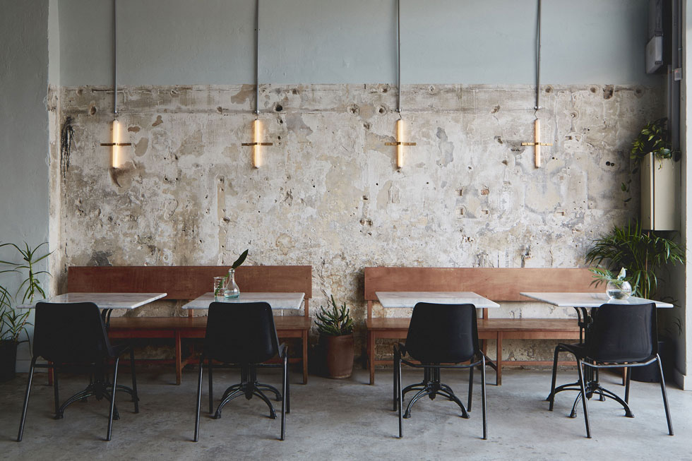 """במסעדת """"מנסורה"""", ברחוב סלמה בדרום תל אביב. האדריכליות והמעצבות נעה קידר וטל ניסים בחרו לשמר בחלל המסעדה את זכרון עברו, באמצעות קיר בטון שנותר חשוף משכבות הצבע ורצפת בטון  אפורה. הריהוט אקלקטי, וגופי התאורה קורצים לימי הפלורסנט  (צילום: מתן כץ)"""