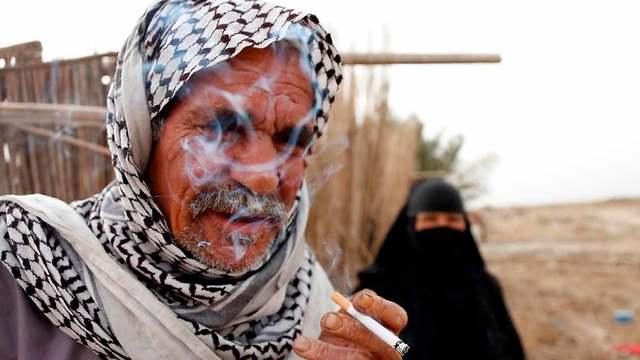 גבר עיראקי מעשן סיגריה (צילום: AFP)