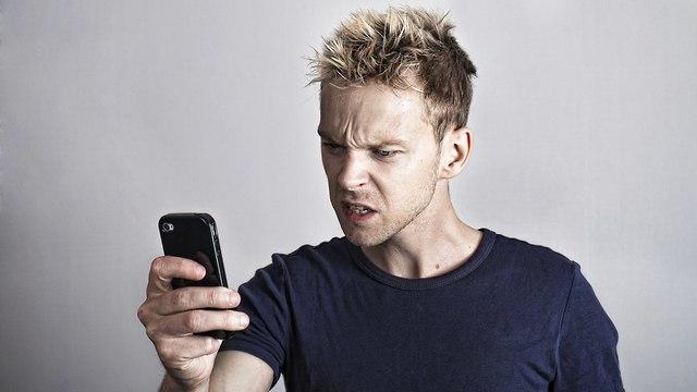 גבר מסתכל על הטלפון שלו כועס (צילום: Shutterstock)