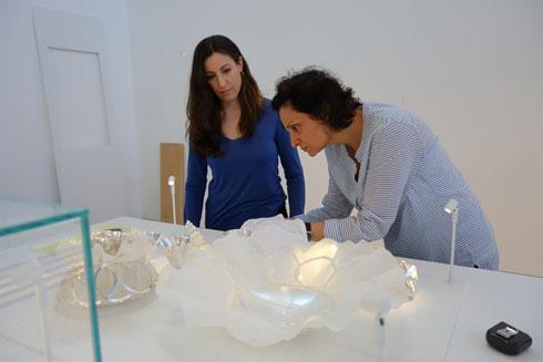 האוצרת (משמאל) בהכנת התצוגה. הקוריאן, שממנו עשויים שולחנות התצוגה, בנוי כמקשה אחת ולובנו מתבלט על רקע חלל התצוגה האפור (צילום: מיכאל יעקובסון)