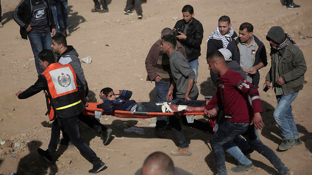 Evacuating a wounded Palestinian during Friday's clashes (Photo: AP)