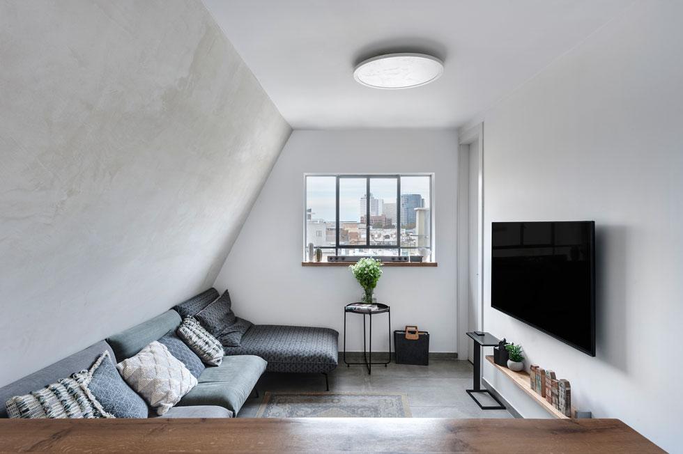 השטח הציבורי של הדירה, המתפרשת על שתי קומות, מוקם דווקא בקומה העליונה, תחת גג הבניין המשופע. שטחו של הסלון רק 8 מטרים רבועים (צילום: עודד סמדר)