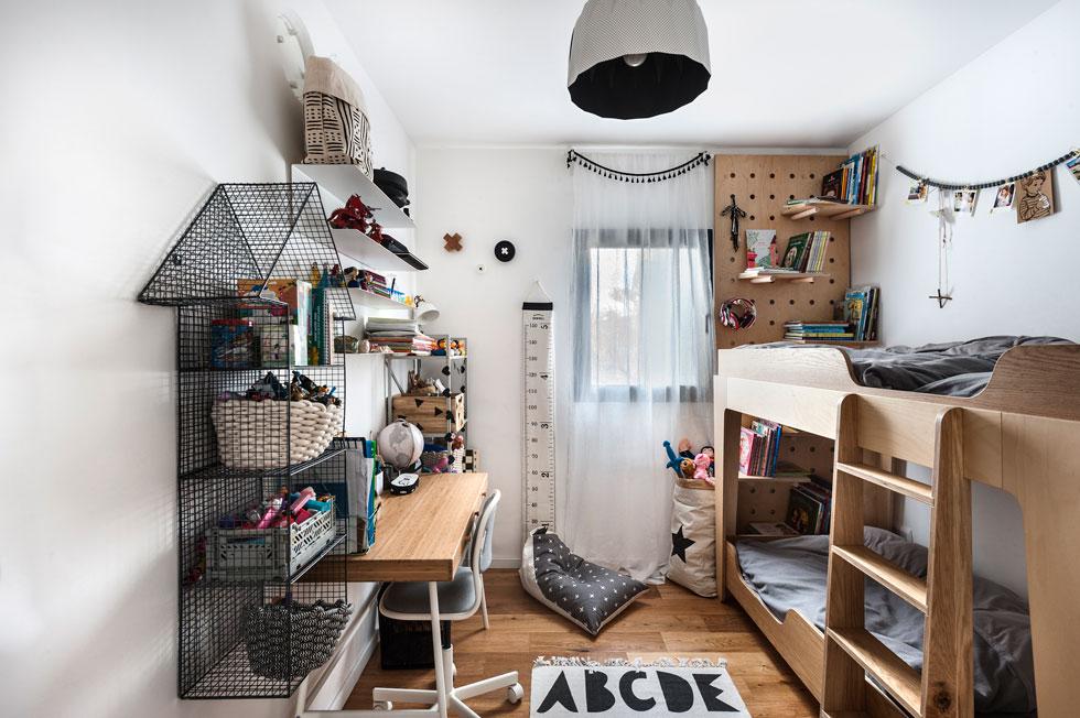 """האח והאחות הגדולים חולקים מיטת קומותיים בממ""""ד שהפך לחדר ילדים. המיטה יוצרה בהזמנה, האבזרים בחדר לוקטו על ידי אם המשפחה אצל יצרנים קטנים בסביבה (צילום: עודד סמדר)"""