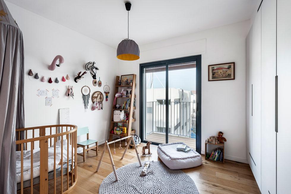 לתינוקת יש חדר עם מרפסת קטנה. על הקיר תלויים אוסף צבעוני של בובות בד, לוכדי חלומות ארוגים ועבודות רקמה קטנות  (צילום: עודד סמדר)