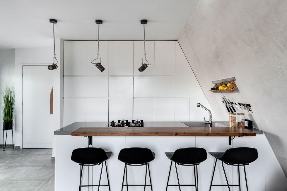 קיר הארונות והאי במטבח בנויים בהתאמה לשיפוע הגג. האי משמש לבישול ולאכילה, על משטח העץ שהורכב עליו בהגבהה. המקרר הוסווה בקיר הארונות הלבנים  (צילום: עודד סמדר)