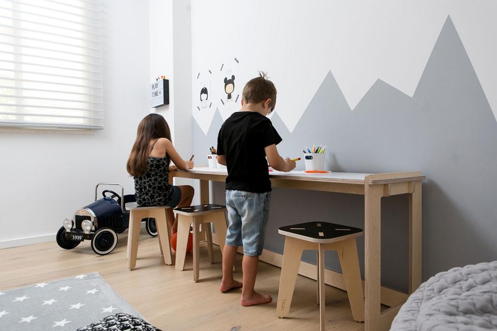 """הקיר בחדר המשחקים נצבע בדוגמה גרפית של רכס הרים, ואליו הוצמד שולחן ארוך עם שרפרפים. """"מעבר לשינוי הדרמטי במראה ובהרגשה"""", אומרות המעצבות, """"רצינו להביא לכך ששרון תרגיש כאילו היא נכנסה לדירה חדשה, רק בלי לקום מהספה""""  (צילום: שירן כרמל)"""