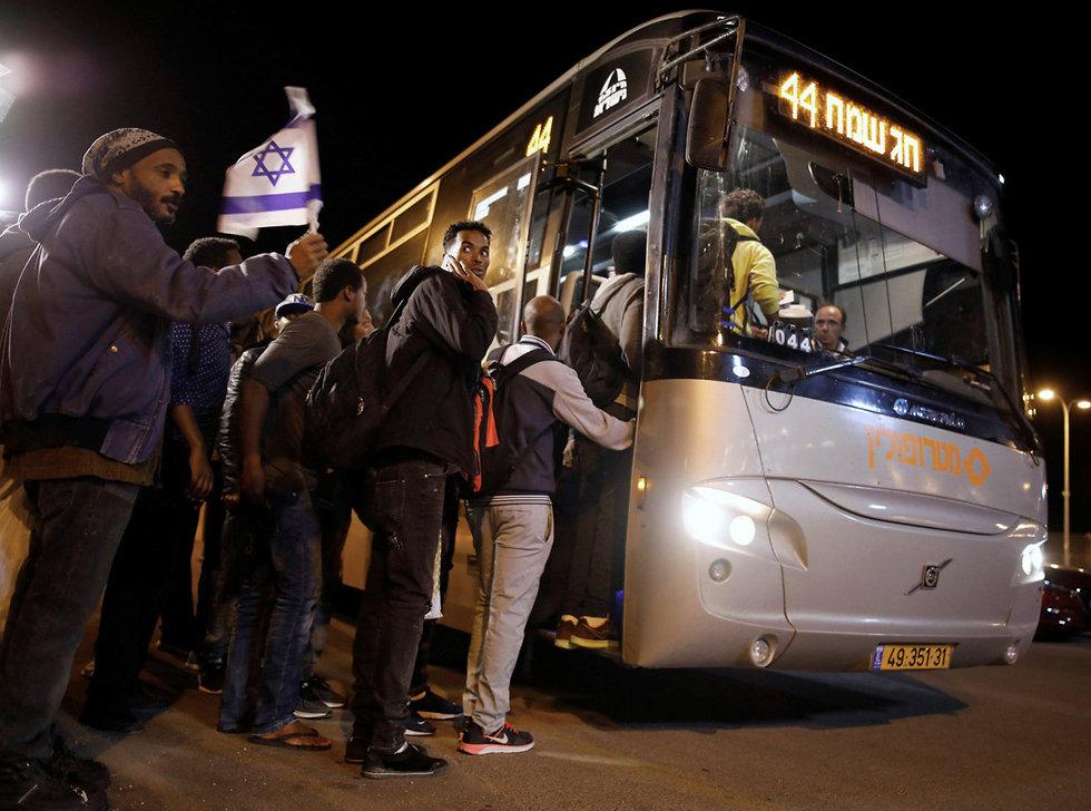 מבקשי מקלט עולים לאוטובוס (צילום: רויטרס)