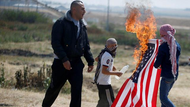The American flag was also torched (Photo: Reuters)