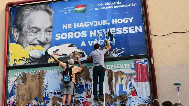 פעילים מסירים שלטים נגד ג'ורג' סורוס הונגריה ()