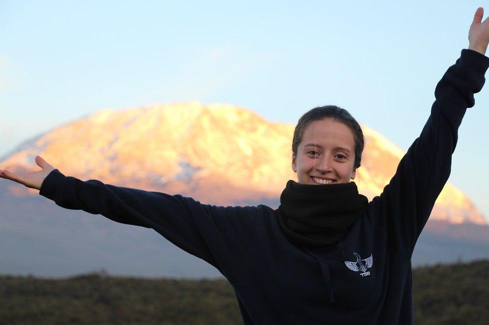 נגה ברקן עומדת עם ידיים פרושות על פסגת הר הקילימנג'רו (צילום: יובל פומרנץ)
