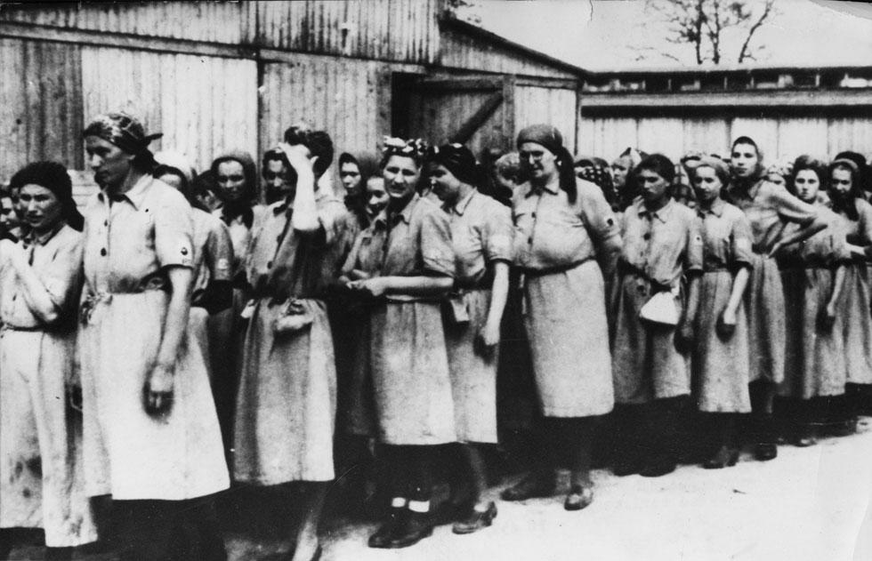 """אסירות באושוויץ. """"כל אישה שהגיעה למחנה ציינה את כישוריה, בתקווה שהעבודה עשויה להציל את חייה. הסטודיו לתפירה עילית היה מקום מועדף לעבודה, מכיוון שהנשים שעבדו בו זכו ל'מותרות' כמו גישה למים, כביסה ותגמול מהלקוחות"""" (צילום: AP)"""