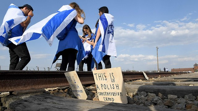 """Teens during the traditional journey to Poland, standing by the Auschwitz rail track and sign calling the place """"a Polish concentration camp"""" (Photo: AFP)"""