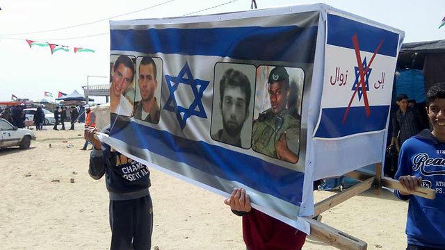 ארון קבורה עם תמונות החיילים החטופים ()