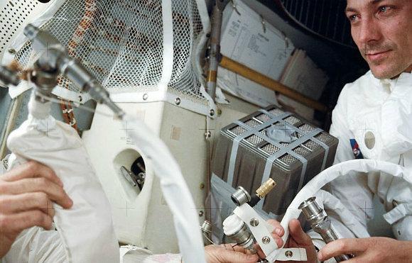 """ג'ק סוויגרט עם המתקן המאולתר לתיאום מסנני האוויר (צילום: נאס""""א)"""