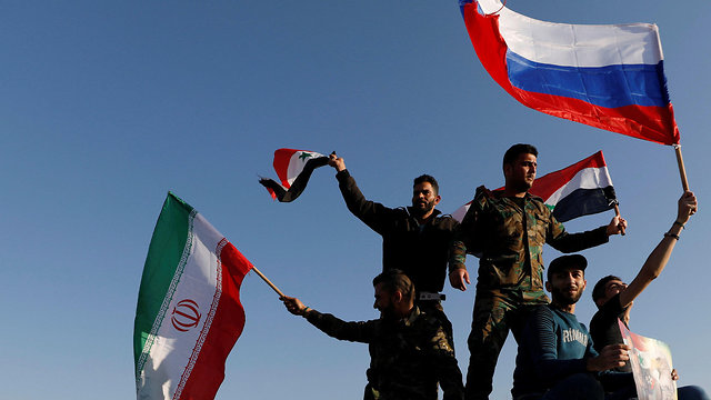 Syrian soldiers waving Syria, Iranian and Russian flags (Photo: Reuters)
