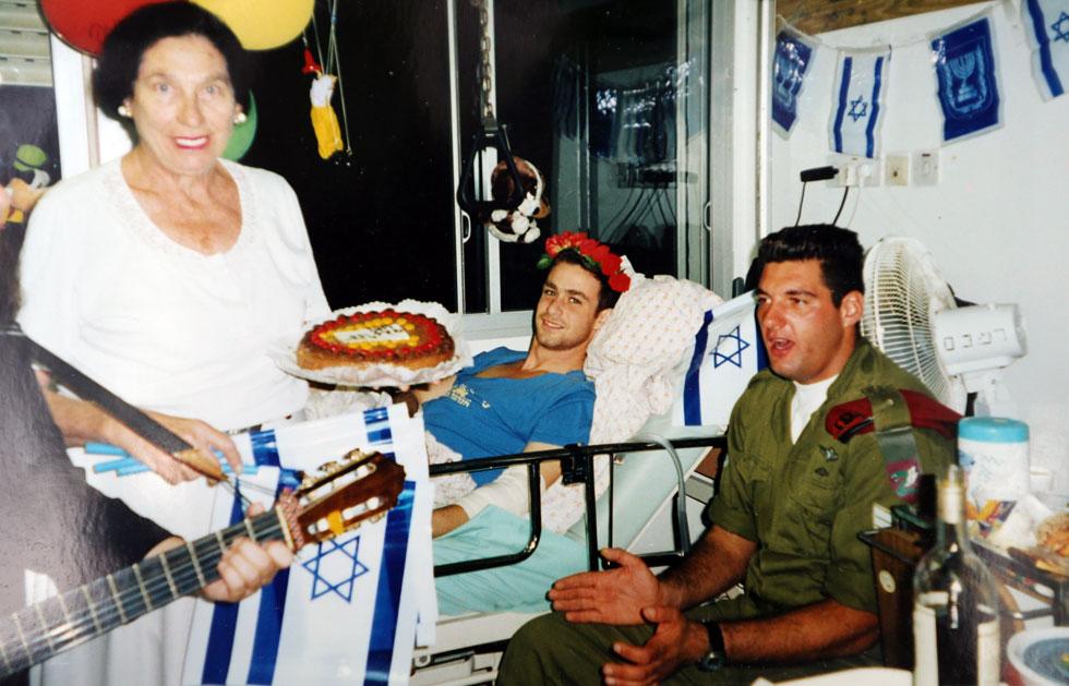 """גורביץ בבית חולים, ליד מיטה של פצוע. """"כשאדם עצוב, הוא חולה. מי ששמח, מבריא ומתחזק"""" (צילום רפרודוקציה: אלעד גרשגורן)"""