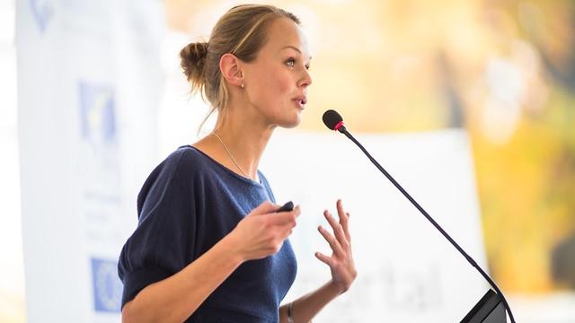 אישה מדברת מול מיקרופון (צילום: shutterstock)