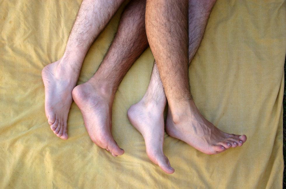 שני זוגות רגליים שעירות על המיטה (צילום: Shutterstock)
