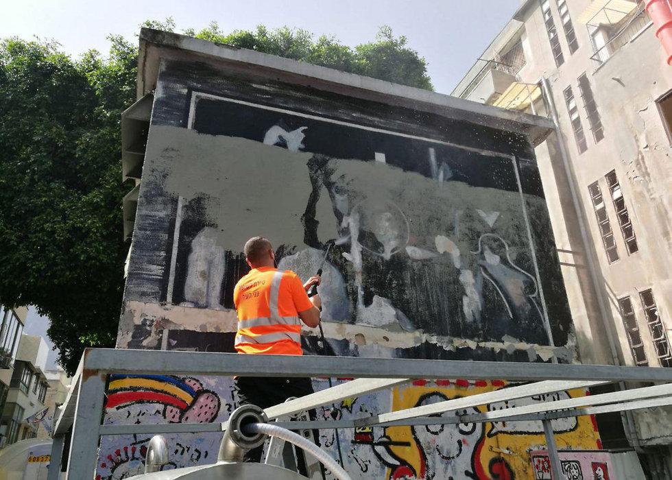 עובד עריית תל אביב מנסה להציל ציור קיר של רצח רבין שצבעו עליו ב פלורנטין ()