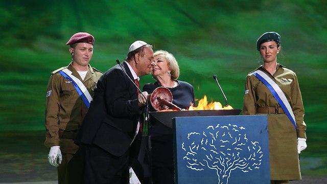 Actors Ze'ev Revach and Leah Koenig light a torch (Photo: Alex Kolomoisky)