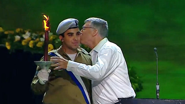Linguist Dr. Avshalom Kor kissing an IDF soldier as he lights a torch (Photo: Herzliya Studios)