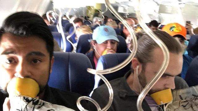 הנוסעים עם מסיכות חמצן (צילום: AP, Marty Martinez)