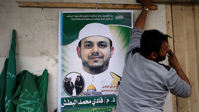 Man puts up poster in Jabalia (Photo: Reuters)