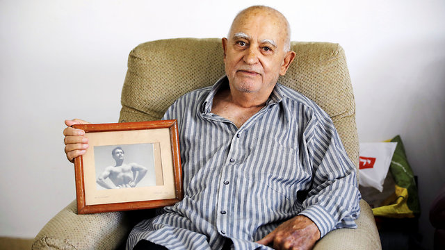 Aharon Ben Hur with a photo of his younger self (Photo: Reuters)