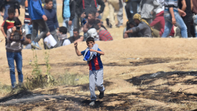 Palestinian child throwing rocks at IDF forces and the Gaza security fence during Gaza border riot (IDF Spokesperson's Unit)