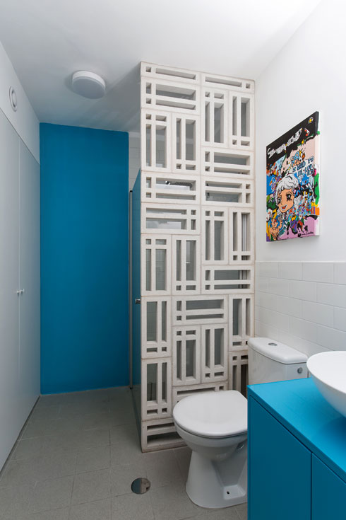 בחדר הרחצה שהוא גם שירותי האורחים הוסתרה מעט המקלחת בעזרת משרבייה מבטון לבן (צילום: שירן כרמל)