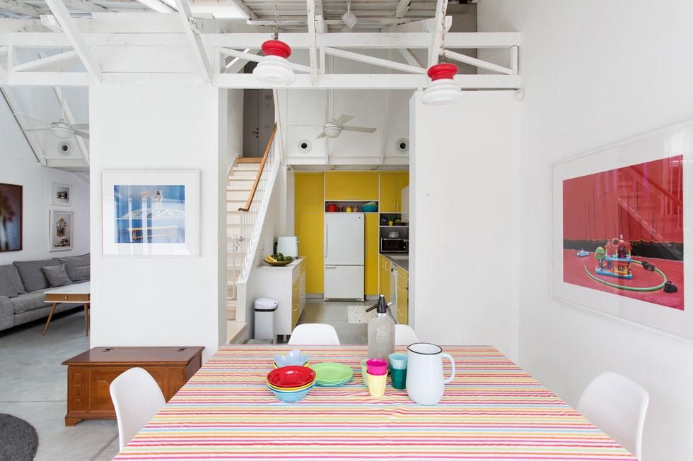 מעל שולחן האוכל ועל העמוד לצדו שני צילומים של יאיר חובב, בכחול ובאדום - שתי עבודות מתוך תשע שבחרו מיכל בהרב ובן זוגה מהאוסף של יפעת גוריון, מייסדת ואוצרת יריד האמנות ''צבע טרי''. ''אנחנו מאוד אוהבים צבעים'', אומרת בהרב, ''וזה לא קשור לזה שיש לנו ילדים קטנים'' (צילום: שירן כרמל)