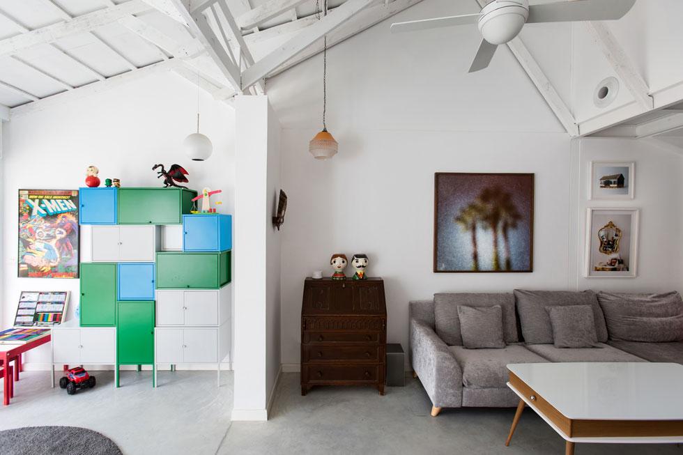 המרפסת הסגורה האחורית הפכה לחלק מהבית. כדי לשלוט על הבלגן בפינת המשחק תכננה האדריכלית מערום של ארוניות אחסון מ''איקאה'', בשלושה צבעים. מעל הספה צילום גדול של ינאי מנחם, ולצדו עבודות צילום של ארתור יעקובוב (למטה) ושל עפרה לפיד (למעלה) (צילום: שירן כרמל)